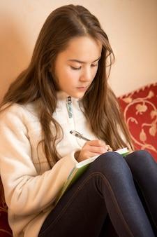 Portrait of brunette teen girl écrit dans le journal à la chambre