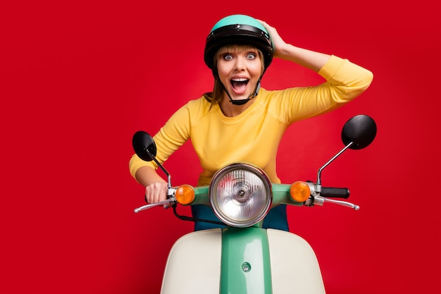 Portrait of cheerful girl conduisant un cyclomoteur voyageant dépêchez-vous sur le mur rouge