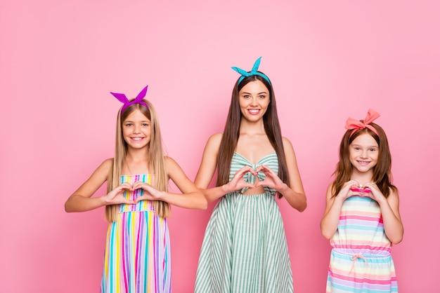 Portrait of cheerful ladies kid faisant des signes en forme de coeur avec leurs doigts portant des bandeaux robe jupe isolé sur fond rose