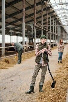 Portrait of content teenage boy in hat standing with pelle dans l'étable, il travaille avec les parents à la ferme