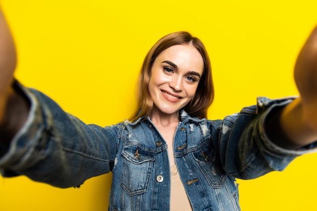 Portrait of cool cheerful girl shooting selfie on front camera isolé sur mur jaune