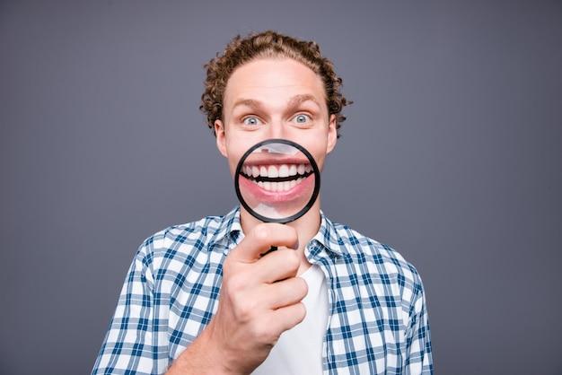 Portrait of crazy guy cheveux ondulés en chemise à carreaux montrer sourire à travers la loupe