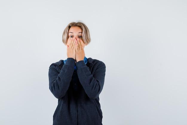 Portrait of cute teen boy gardant les mains sur la bouche en sweat à capuche et à la vue de face agitée