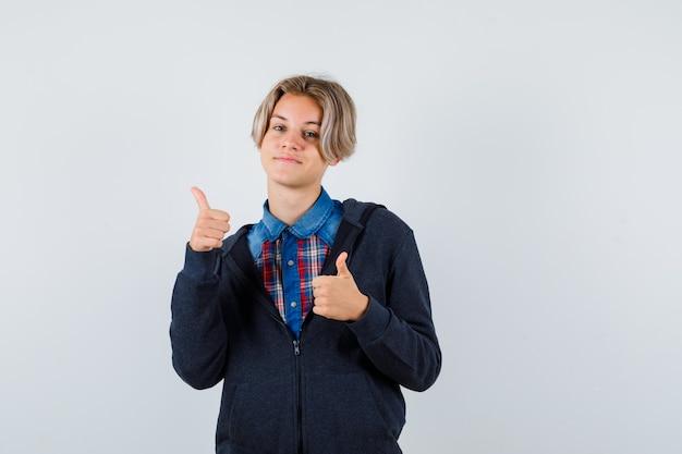 Portrait of cute teen boy montrant double pouce levé en chemise, sweat à capuche et à la vue de face joyeuse