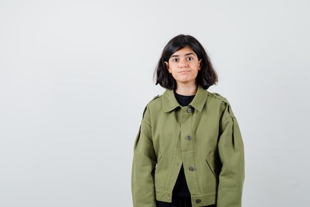 Portrait of cute teen girl in army green jacket et à la vue de face perplexe