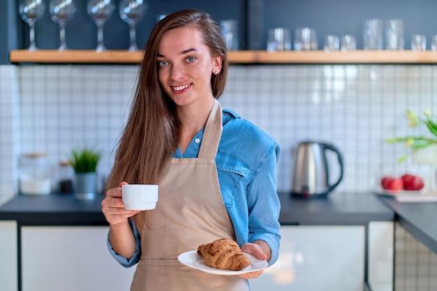 Portrait of cute young happy smiling woman baker tenant une tasse blanche et un croissant de plaque à la cuisine loft