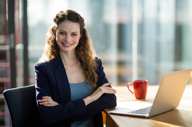 Portrait of female business executive sitting in office with laptop on table