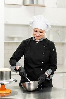 Portrait of friendly smiling woman confiseur professionnel garniture d'un petit gâteau avec de la crème à l'aide d'une poche à douille