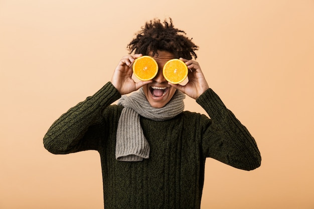 Portrait of funny guy afro-américain portant chandail et écharpe couvrant les yeux avec deux morceaux d'orange, isolé sur mur beige
