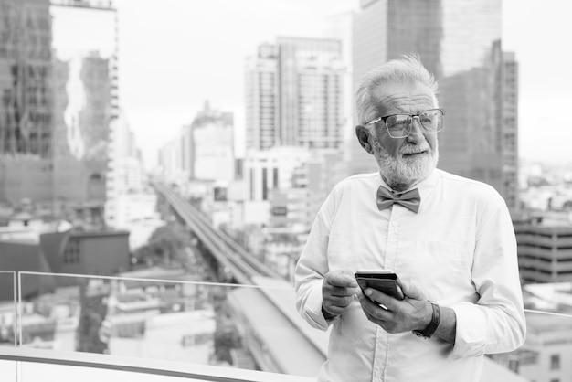 Portrait of handsome senior tourist man portant des vêtements élégants tout en explorant la ville de bangkok en noir et blanc