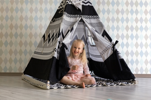 Portrait of happy 3-year-old bambin girl girl smiling while sitting in children play tent