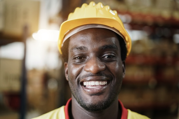 Portrait of happy african worker man looking at camera à l'intérieur du magasin d'entrepôt - focus sur le visage