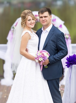 Portrait of happy bride and groom hugging against floral arch