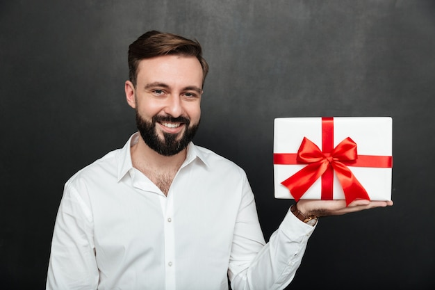Portrait of happy brunette man démonstrating white present box with red bow on camera and smiling over dark grey wall