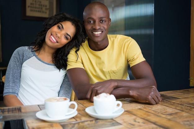 Portrait of happy couple aimant assis à table dans un café