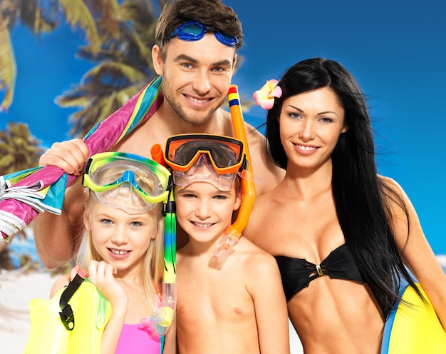Portrait of happy fun belle famille avec deux enfants à la plage tropicale avec masque de protection