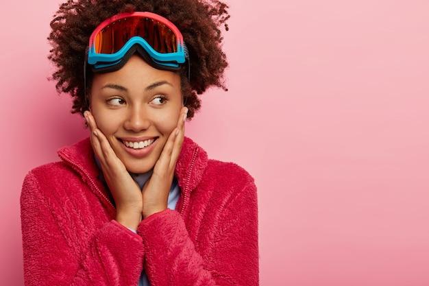 Portrait of happy girl aux cheveux bouclés snowboader bénéficie d'un repos actif, touche les joues doucement, détourne les yeux avec un sourire à pleines dents, porte manteau rouge, lunettes de ski, isolé sur fond rose.
