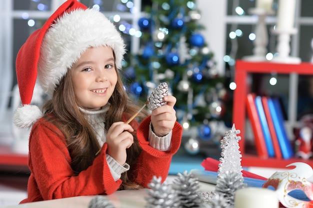 Portrait of happy girl in santa hat prapring pour noël assis à la table