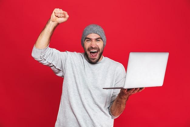 Portrait of happy guy 30 s en tenue décontractée se réjouissant tout en tenant un ordinateur portable en argent isolé