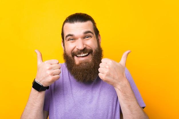 Portrait of happy happy hipster barbu homme montrant les pouces vers le haut sur fond jaune