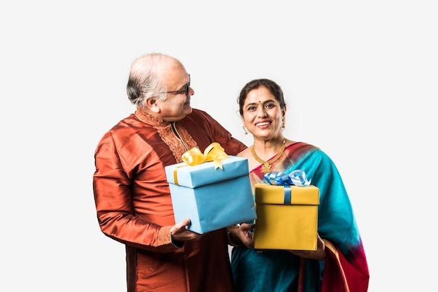 Portrait of happy indian asiatique senior ou couple de retraités tenant des coffrets cadeaux isolés sur fond blanc