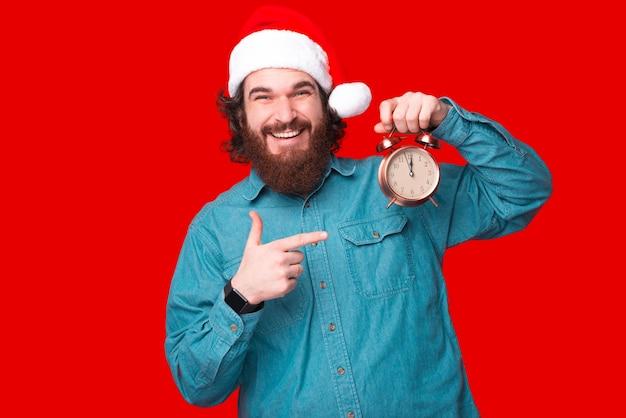 Portrait of happy man with beard in casual wearing santa claus pointing at réveil et est prêt pour le réveillon du nouvel an
