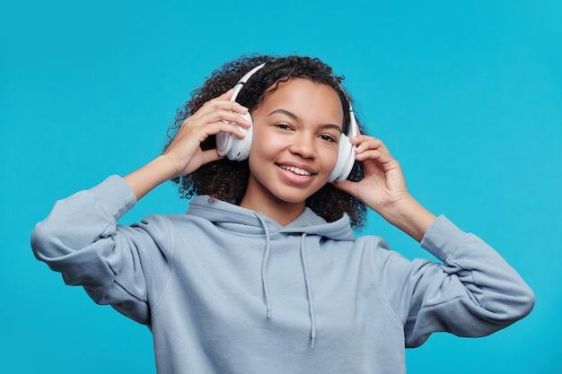 Portrait of happy pretty black girl in hoodie réglage des écouteurs sans fil tout en écoutant de la musique sur fond bleu