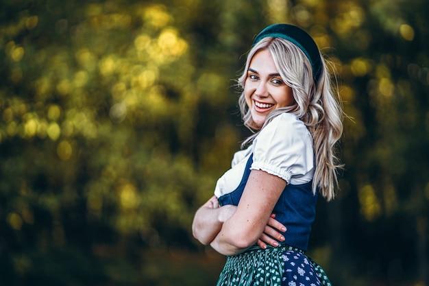 Portrait of happy pretty blonde girl in dirndl, robe traditionnelle du festival de la bière, debout à l'extérieur avec des arbres colorés estompés derrière