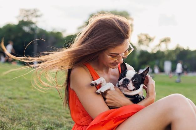 Portrait of happy pretty woman sitting on grass in summer park, holding boston terrier dog, smiling humeur positive, vêtue d'une robe orange, style branché, lunettes de soleil, jouant avec animal de compagnie