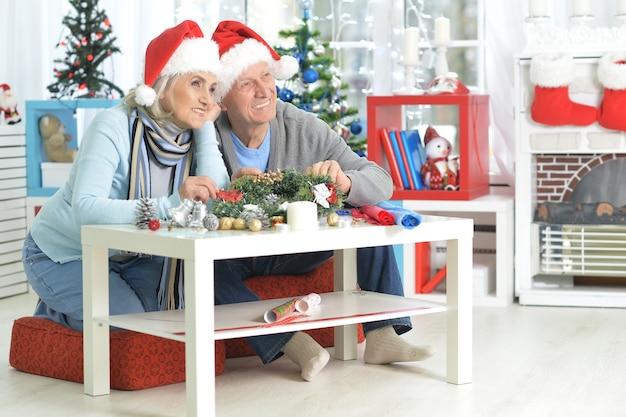 Portrait of happy senior couple in santa hats se préparant pour noël