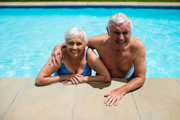 Portrait of happy senior couple relaxant ensemble dans la piscine