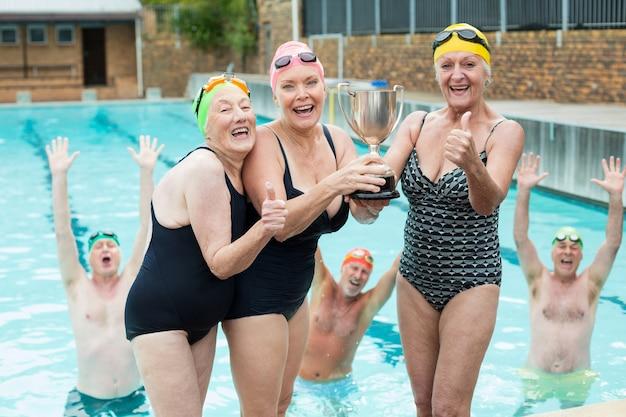 Portrait of happy senior female nageurs holding trophy at poolside