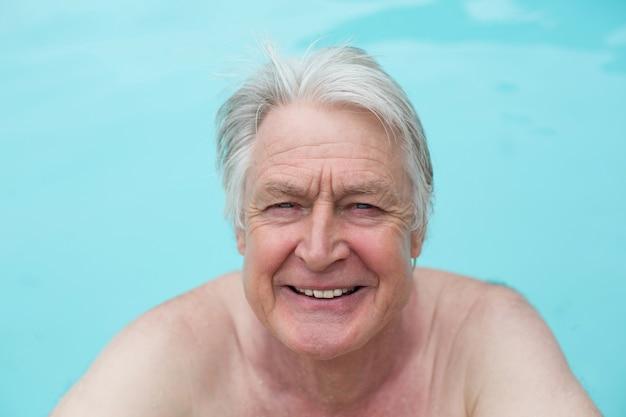 Portrait of happy senior man nager dans la piscine