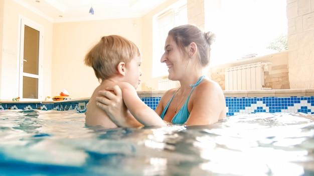 Portrait of happy smiling baby boy apprendre à nager avec la mère dans la piscine. famille s'amusant et se relaxant dans la piscine