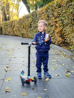 Portrait of happy smiling baby boy with scooter holding juice in park