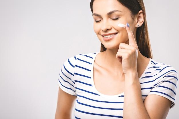 Portrait of happy smiling belle jeune femme toucher la peau ou appliquer la crème