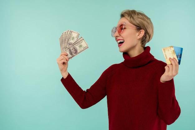 Portrait of happy smiling caucasian woman holding carte de crédit et de l'argent en dollars usa tout en regardant la caméra isolée sur fond bleu.