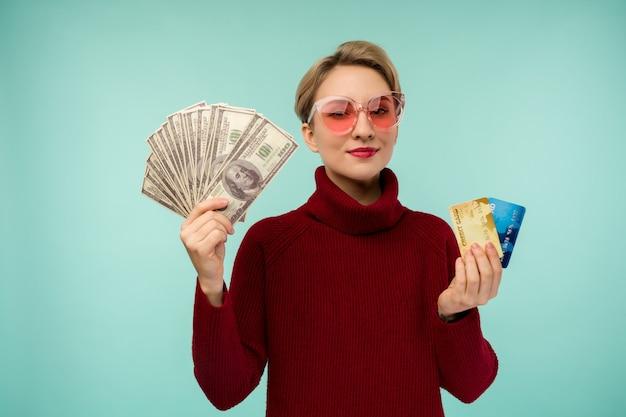 Portrait of happy smiling caucasian woman holding carte de crédit et argent dollars usa