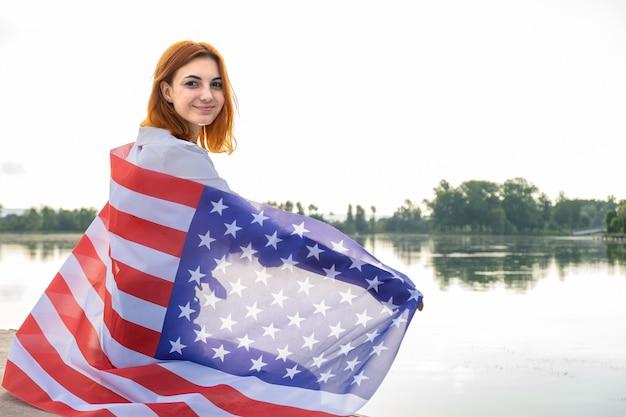 Portrait of happy smiling girl aux cheveux rouges avec le drapeau national des usa sur ses épaules