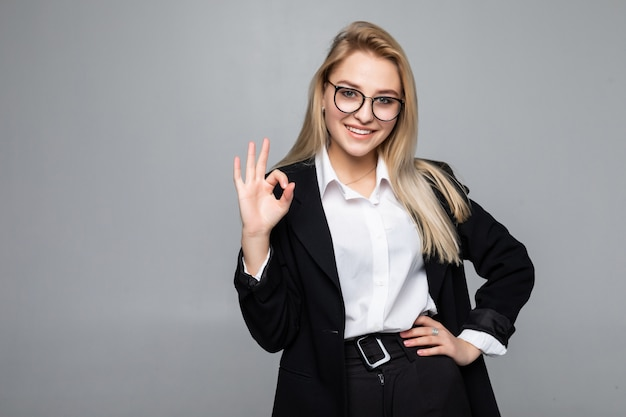 Portrait of happy smiling young cheerful businesswoman montrant signe correct isolé