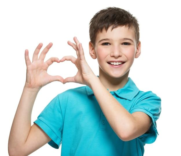Portrait of happy teen boy avec une forme de coeur isolé sur blanc