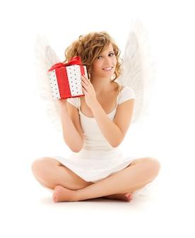 Portrait of happy teenage ange fille avec cadeau sur mur blanc