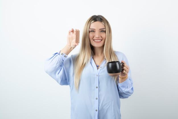 Portrait of happy woman holding tasse de boisson chaude avec barre de chocolat contre le mur blanc