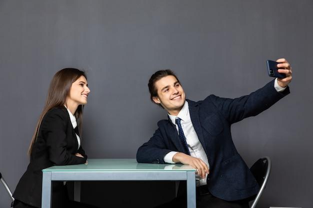 Portrait of a happy young business couple assis sur le bureau portant des costumes en tenant un selfie isolé
