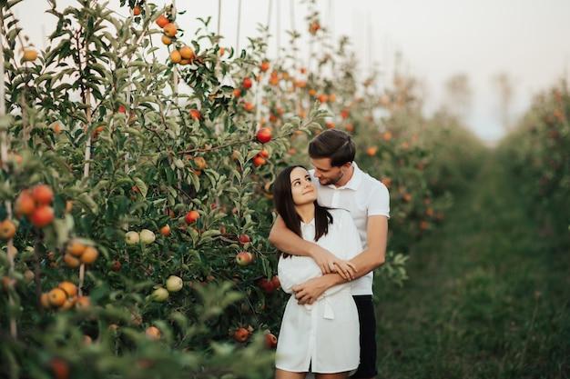 Portrait of happy young couple en étreignant dans le verger d'automne parmi les pommes rouges mûres sur le vert à l'extérieur