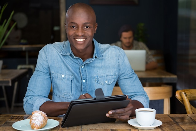 Portrait of happy young man using tablet computer at table in coffee shop
