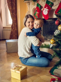 Portrait of happy young mother hugging her 1 an baby boy at christmas tree