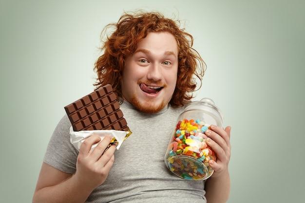 Portrait of happy young redhead barbu homme regardant la caméra avec une expression joyeuse