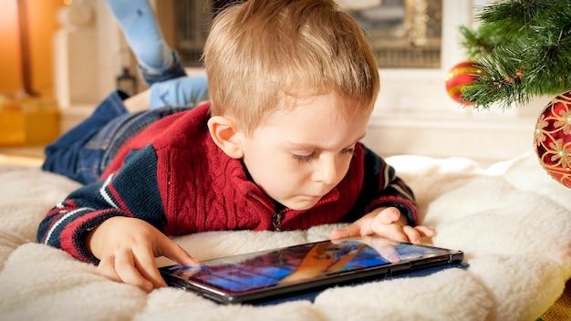 Portrait of little baby boy with tablet allongé sur le sol sous l'arbre de noël le matin du nouvel an