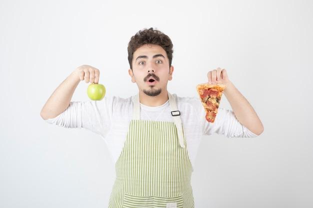 Portrait of male cook holding pizza et pomme verte sur blanc